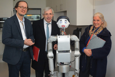 Discussing the future of excellence in research (from left): CITEC Coordinator Prof. Dr. Helge Ritter, Parliamentary State Secretary Klaus Kaiser, and Minister Isabel Pfeiffer-Poensgen pose with the service robot Floka. Photo: Bielefeld University