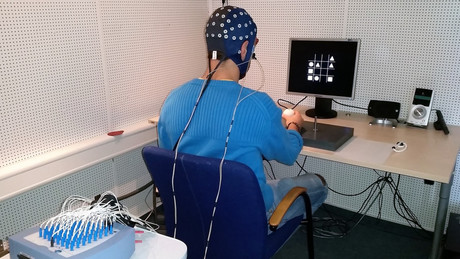 1. During the experiment, test subjects wear a cap that measures the electrical activity of their brain waves in the form of an EEG. Photo: CITEC/Bielefeld University