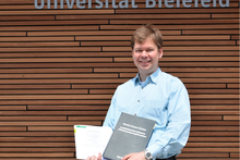Dr. Dirk Koester with his post-doctoral habilitation thesis and habilitation degree certificate from Bielefeld University. Photo: CITEC/Bielefeld University