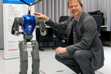 "The small humanoid robot COMAN still has some ""growing"" to do before it can interact ""eye to eye"" with human adults. Professor Dr. Jochen Steil is leading the new research project. Photo: Bielefeld University"